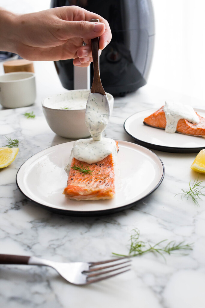 A hand spooning creamy dill sauce on a piece of salmon
