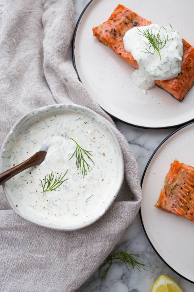 A bowl of creamy dill sauce with plates of salmon to the side