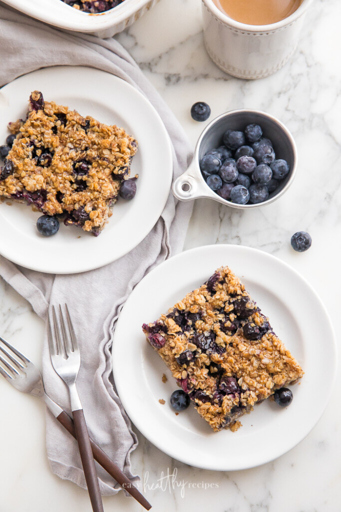 Two slices of blueberry baked oatmeal on white plates