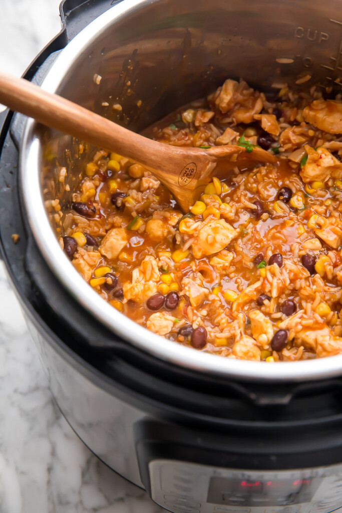 Cooked burrito bowl chicken in an instant pot with a wooden spoon