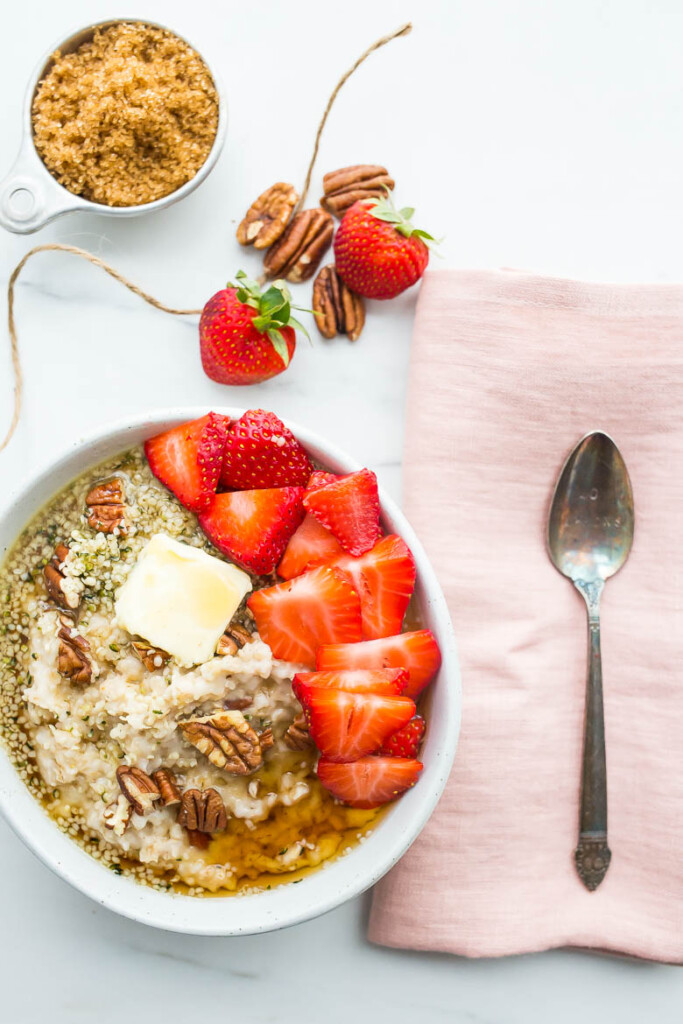 White bowl of oatmeal with strawberries, butter, hemp seeds, pecans, brown sugar, and maple syrup next to pink napkin and spoon.