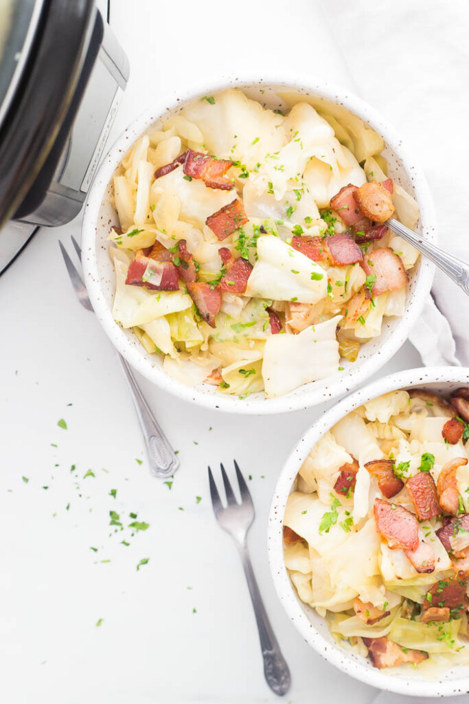 Two speckled bowls filled with crockpot cabbage and topped with bacon and parsley next to crockpot with forks.