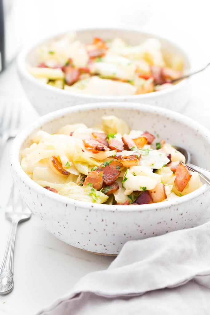 white speckled bowl of crockpot cabbage with bacon on top.