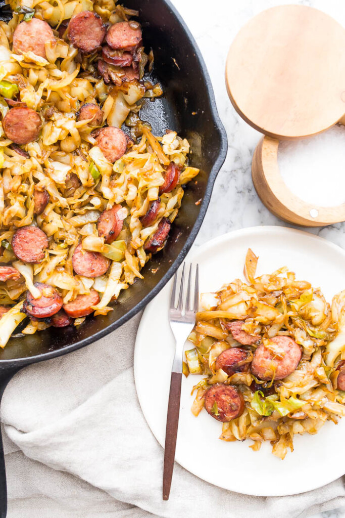 image of kielbasa and cabbage in cast iron skillet and on white plate with fork and salt.
