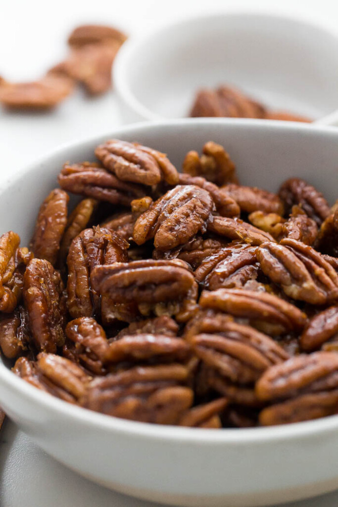 close up of glazed pecans in white bowl.