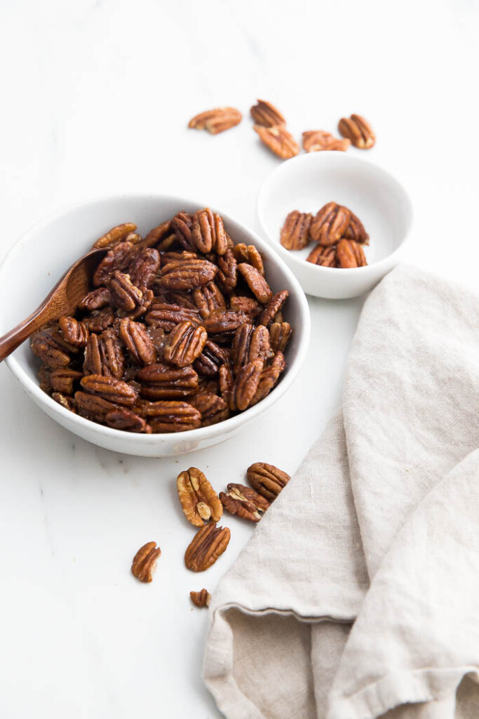 white bowl of glazed pecans with wooden spoon.