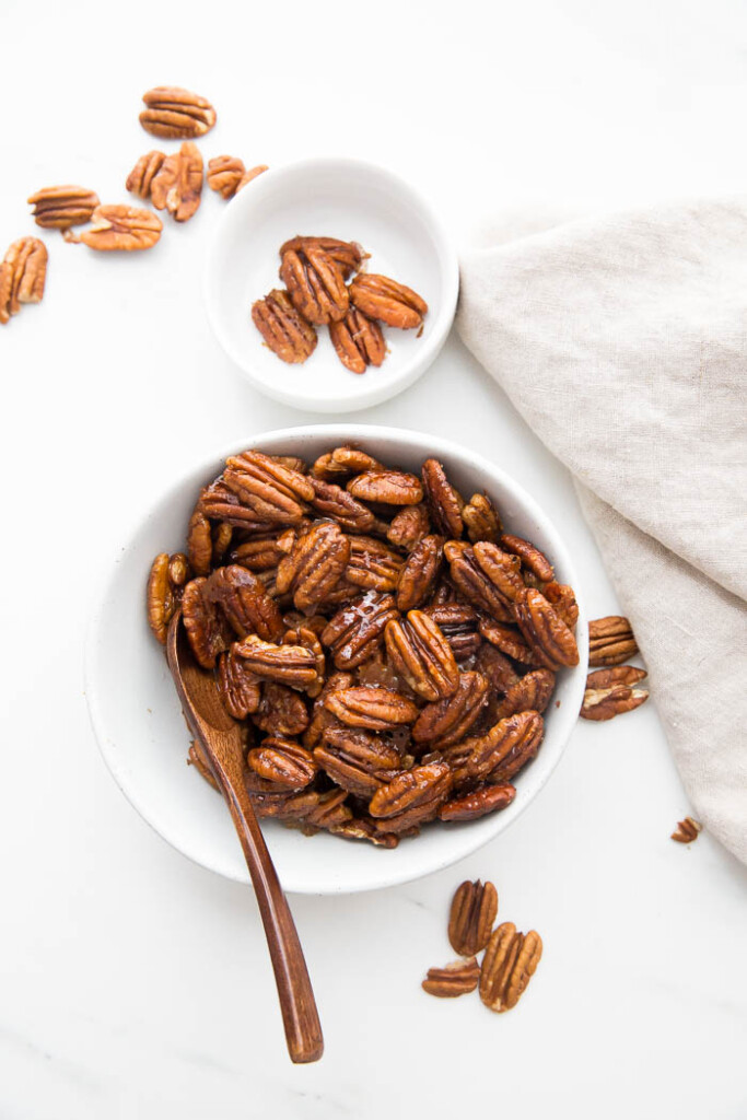 Overhead photo of glazed pecans in white bowl with wooden spoon.
