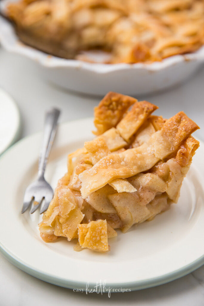 Side profile of sliced apple pie with fork.