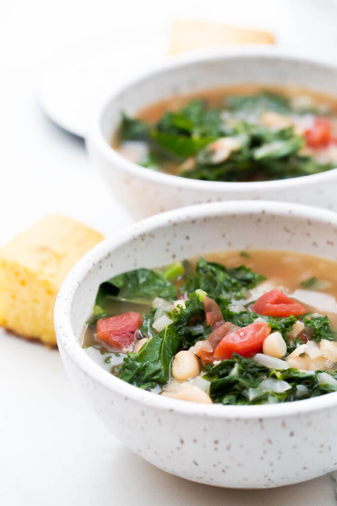 close up photo of kale and white bean soup in white bowl with corn bread