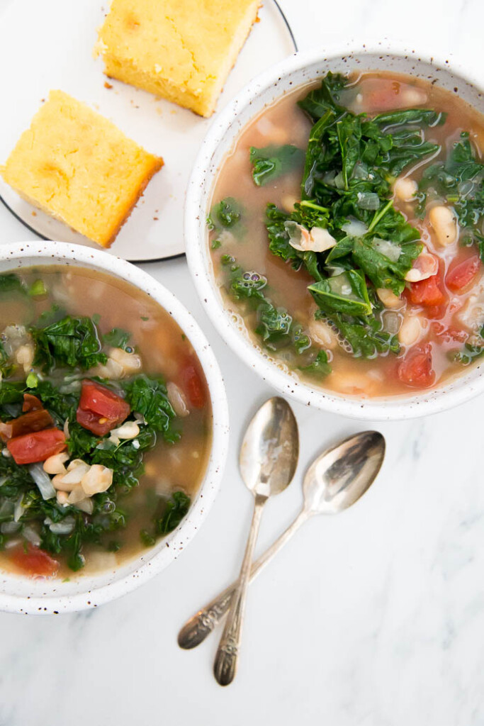 overhead shot of kale and white bean soup with spoons