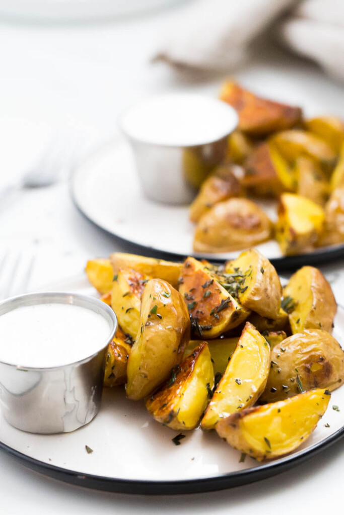 close up image of rosemary roasted potatoes on white plate with sauce.