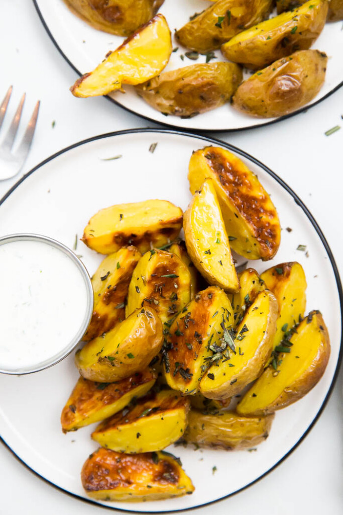 overhead shot of rosemary roasted potatoes on white plate with lemon garlic sauce