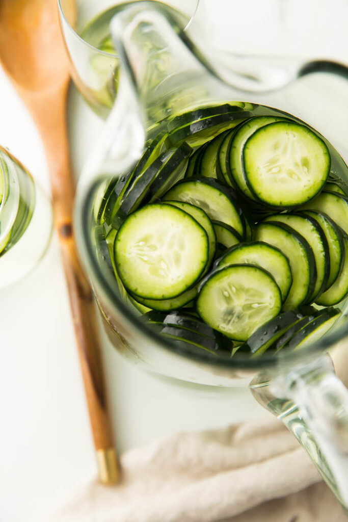 overhead shot of cucumbers in glass water pitcher