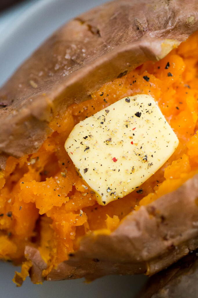 close up image of sweet potato with salt, pepper, and butter.