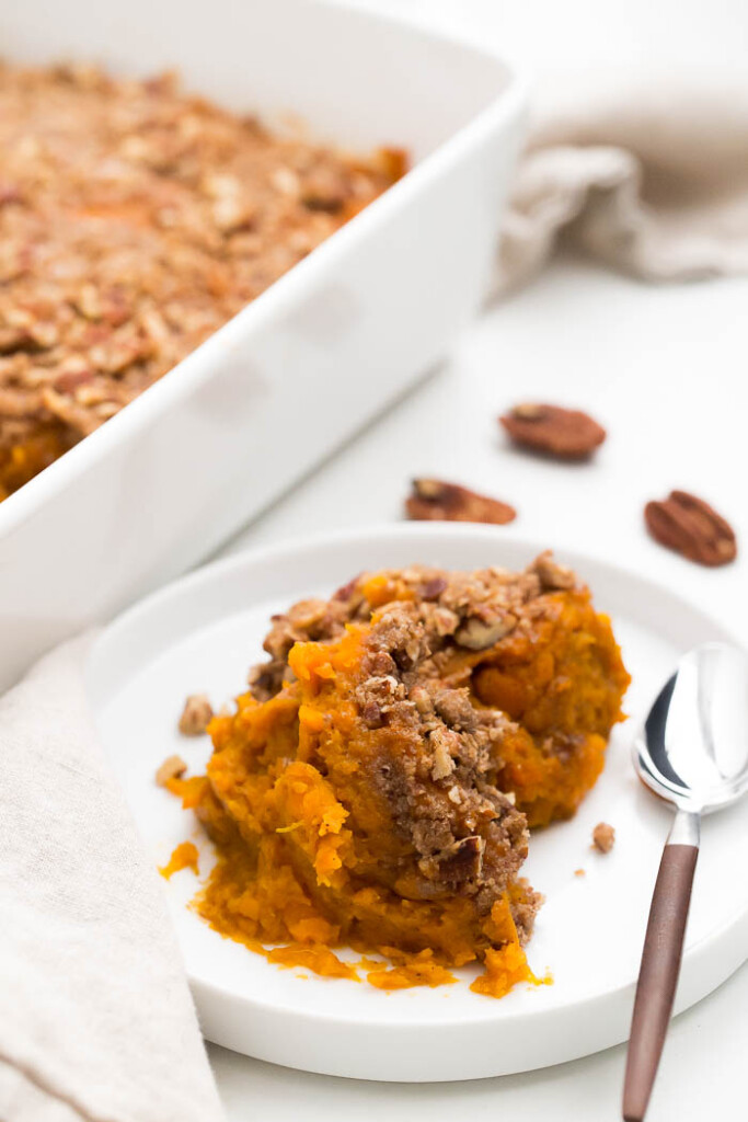 close up image of sweet potato casserole on white plate.