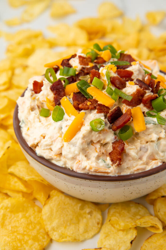 Bowl of loaded baked potato dip surrounded by chips