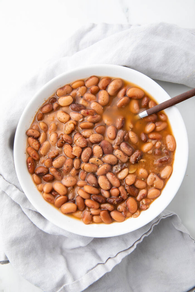 White bowl of slow cooker pinto beans with a spoon