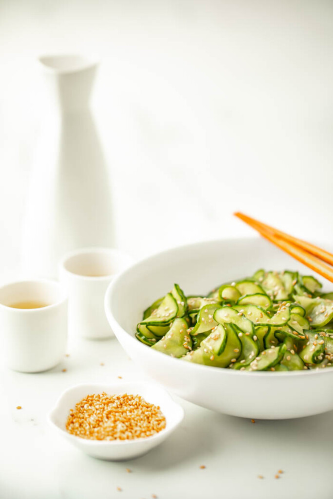 Simple Asian cucumber salad in a white bowl surrounded by bottles of sake and sesame seeds