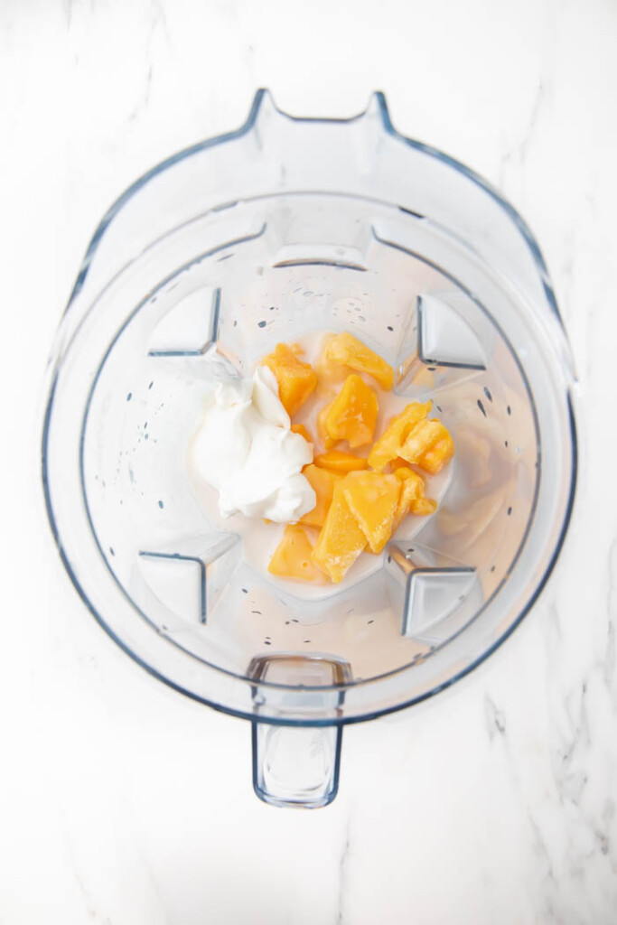 Ingredients for mango pineapple smoothie in a blender