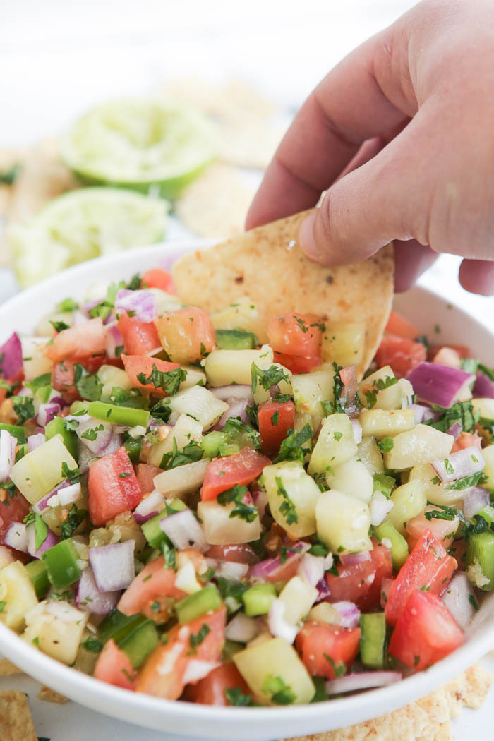 Chip being dipped into cucumber salsa