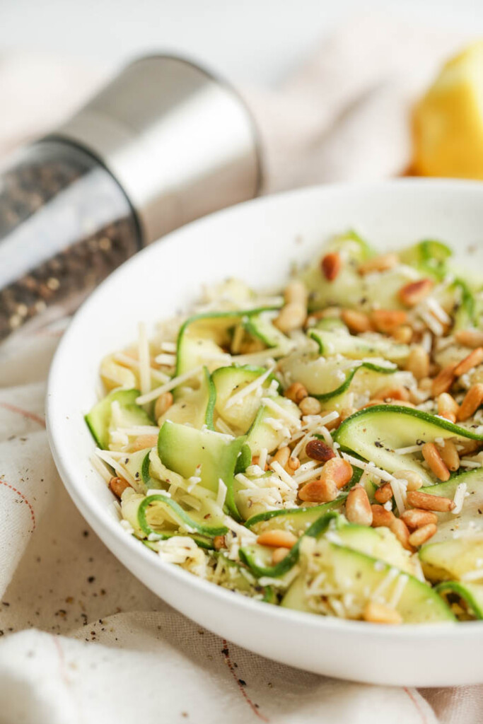 Bowl of zucchini salad next to a pepper grinder