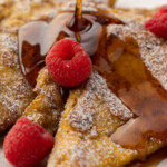 Sugarfree syrup pouring on top of keto french toast with powdered erythritol and raspberries