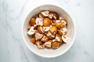 A white bowl full of uncooked and unseasoned mushrooms on a white counter
