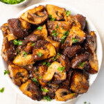 Overhead shot of a white bowl full of air fryer mushrooms topped with bits of parsley