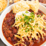 A bowl of bison chili with cornbread and topped with cheese and sour cream