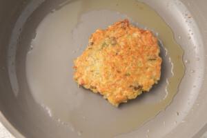 Fried vegan latke in a grey nonstick pan