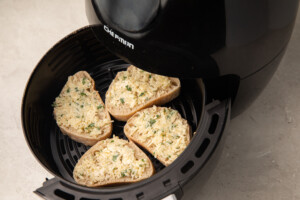 French bread with butter, garlic, parsley, and parmesan in an air fryer bowl