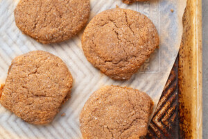Baked ginger snap cookies on a parchment paper lined baking sheet