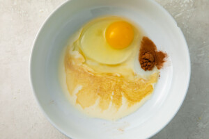 Ingredients for egg wash in a white mixing bowl