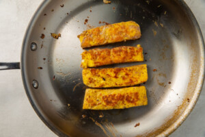 Four fried toast sticks in a medium-sized silver skillet