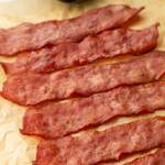6 slices of turkey bacon laid diagonally across a sheet of parchment paper