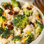 Close up photo of a white bowl of Amish broccoli salad, taken from the side