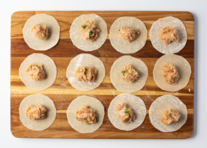 Wonton wrappers on a cutting board, filled with chicken gyoza filling