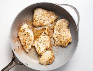 Italian seasoned chicken cutlets in a pan