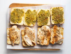 Ciabatta rolls with pesto and chicken on a cutting board
