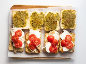 Ciabatta roll with pesto, chicken, mozzarella, and tomatoes, on a cutting board