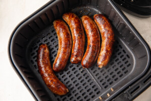 Cooked sausages in an air fryer basket