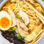 Spicy Chicken Ramen in a bowl topped with a soft boiled egg, scallions, and sesame seeds.