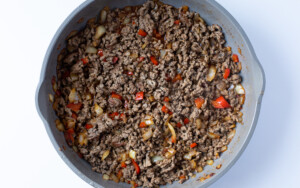 Ground beef with onion, beef broth, bell pepper, and spices in skillet