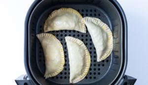 Unbaked empanadas in an air fryer basket