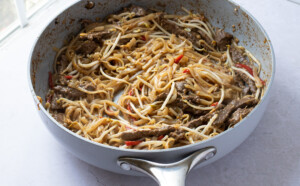 Beef pad thai with bean sprouts in large skillet