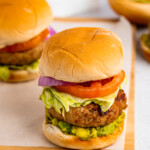 two air fryer turkey burgers with lettuce, tomato, red onion, and avocado