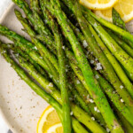 Asparagus on a plate with lemon slices.