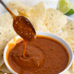 Tomatillo red chili salsa drizzling off a spoon into a white bowl of salsa surrounded by corn tortilla chips
