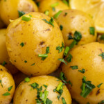 close up image of steam potatoes on a plate with a lemon