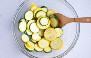 Squash discs in a large mixing bowl with a wooden spoon